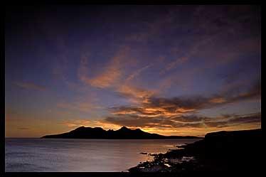 Zapad slunce nad ostrovem Rum - foceno z ostrova Eigg
